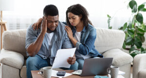 A Couple on the couch looking worried as tFamily Financial Crisis Concept. Depressed Black Couple Looking At Invoice, Not Able To Pay Huge Bills, Suffering From Coronacrisis At Home