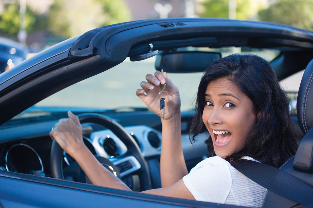 woman in the car smiling holding her keys in the front seat