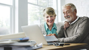 older couple man and woman smiling at computer screen